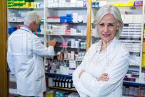 Pharmacist standing with arms crossed and co-worker checking med