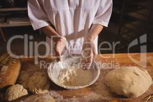 Mid-section of female baker spreading flour in a bowl