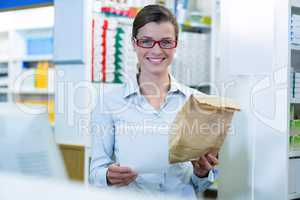 Pharmacist holding prescription and medicine package in pharmacy