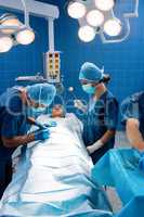 Surgery team operating a patient in an operating room