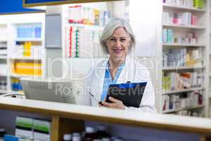 Smiling pharmacist holding a clipboard in pharmacy