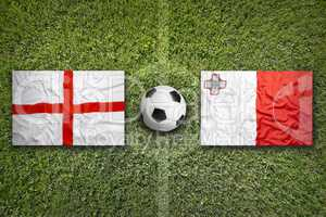 England and Malta flags on soccer field