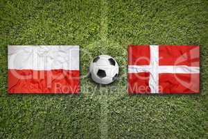 Poland and Denmark flags on soccer field