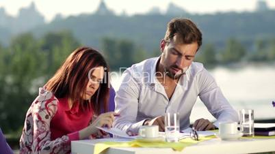 Two business partners signing a contract outdoors