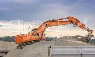 Excavator loading ballast in a trailer