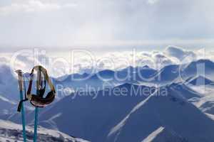 Ski mask on ski poles in evening sunlight mountains