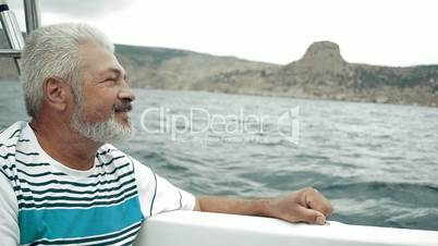 Senior Man Sitting On Boat Looking To The Sea