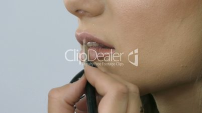 Professional Make-Up Model Applying Lipgloss Brush