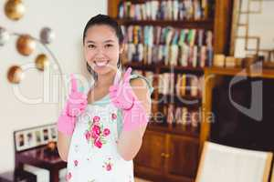Composite image of woman wearing rubber gloves giving thumbs up