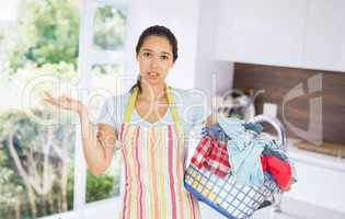 Composite image of puzzled young woman holding laundry basket full of dirty laundry