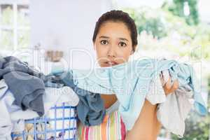 Composite image of frowning woman taking out dirty laundry