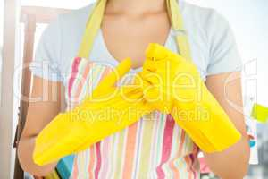 Composite image of woman taking off her rubber gloves