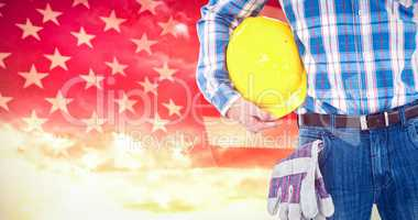 Composite image of manual worker with hard hat and gloves
