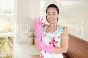 Composite image of woman putting on plastic gloves