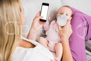 Mother using mobile phone while feeding her baby with milk bottle