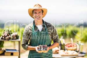 Portrait of a smiling farmer holding box of fig