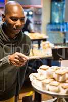Smiling man purchasing sweet food