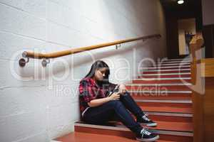Upset female student sitting on staircase