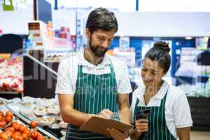 Staff writing on clipboard in organic section