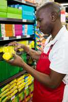 Male staff arranging goods on shelf in grocery section