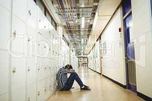Depressed student sitting in locker room