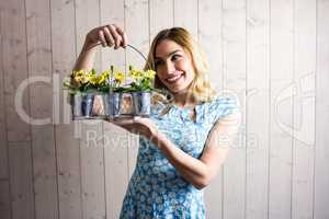 Woman holding a basket of plant pots against texture background