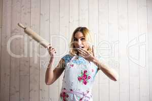 Woman in apron holding a rolling pin against texture background
