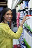 Woman buying milk from dairy section