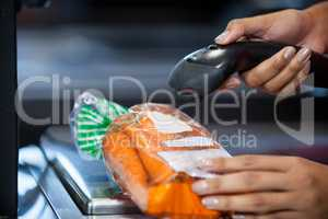 Woman scanning goods at checkout counter