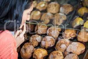 Thoughtful woman selecting sweet food