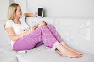 Mother using digital tablet while feeding her baby with milk bottle