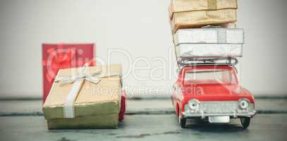 Toy car carrying christmas present on wooden plank