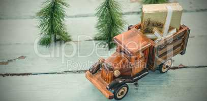 Toy tempo carrying christmas present on wooden plank