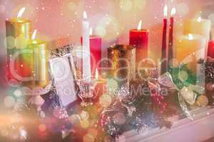 Candles and christmas decorations arranged on fireplace