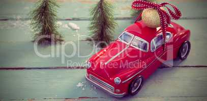 Toy car carrying christmas bauble ball on wooden plank