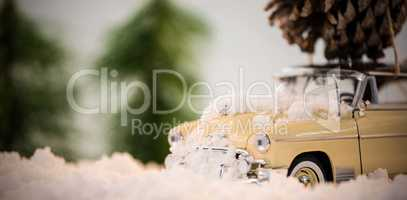 Toy car carrying pine cone on fake snow