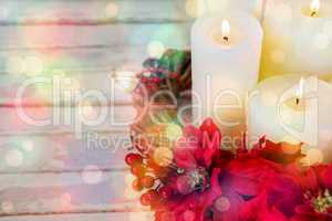 Candles decorated with flowers nest basket on wooden plank