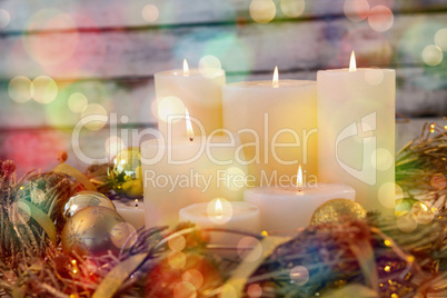 Candles and bauble ball in nest basket on wooden plank