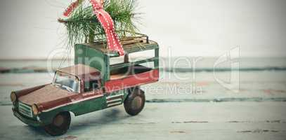 Toy tempo carrying christmas fir on wooden plank