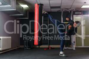 Training time. Image of muscular man boxing at gym