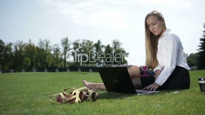 Young business woman working on laptop outdoor