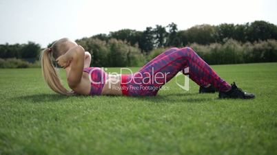 Healthy young blonde woman doing crunches