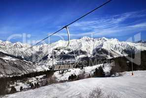 Ski slope and chair-lift in snow winter mountains at sun windy d