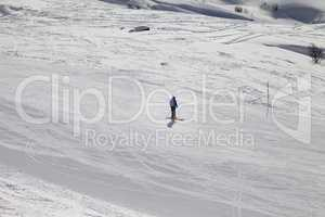 Skier on ski slope at sun winter evening