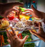 Human hands reaching for sweet cake at night in the open refrige