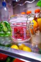 Fresh raspberries in a glass jar on a shelf open refrigerator