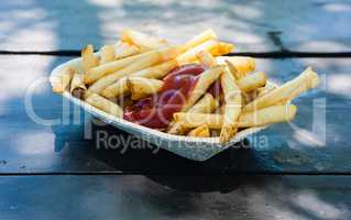 French fries with ketchup in paper tray.