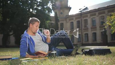 Handsome focused student studying on campus lawn