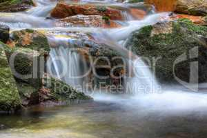 Long exposure of the water flowing over boulders