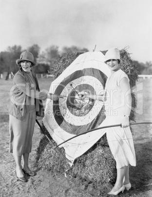 Women with bulls eye in archery target